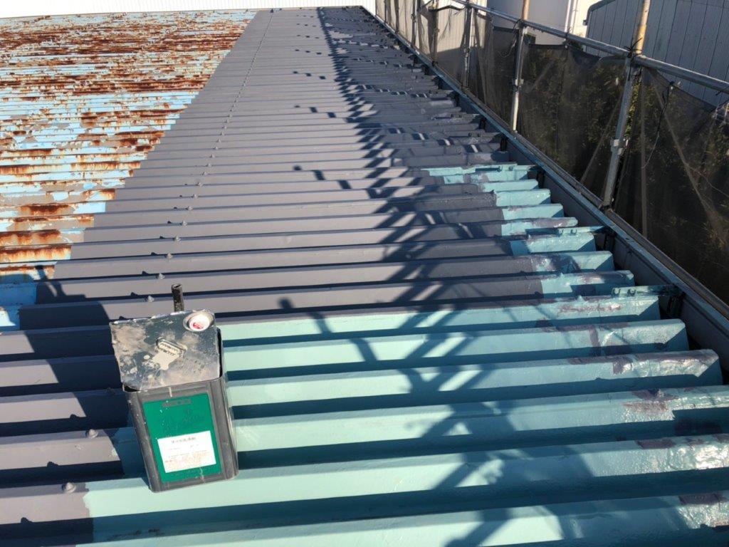 折板屋根にトップコートの塗装中